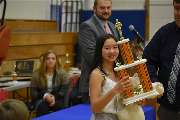 Student holding her grand championship trophy