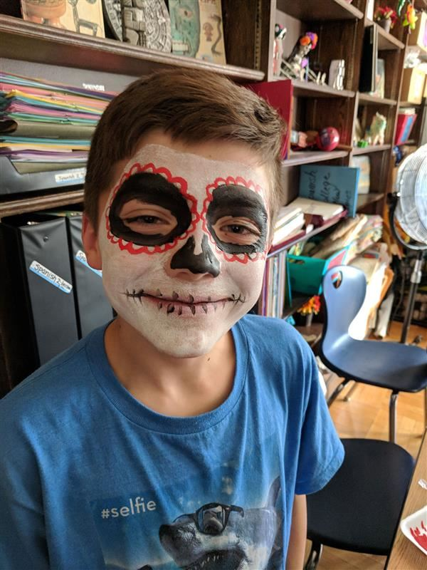 Student wearing red white and black face paint for a day of the dead festival