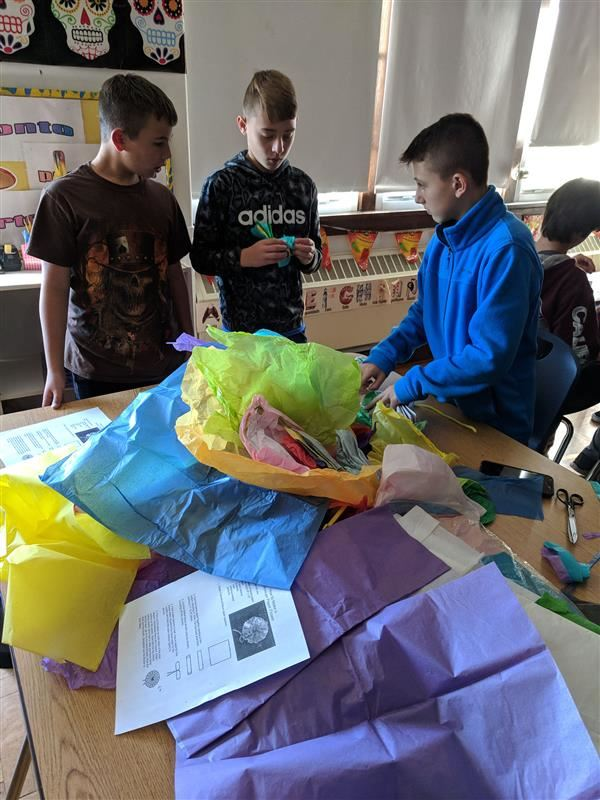 Three students using multi-color tissue paper for crafts