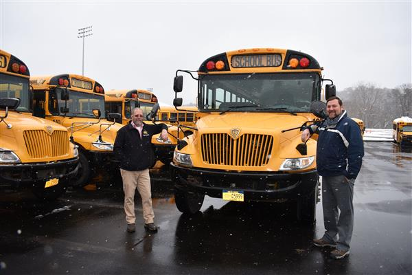 Jeff DeLucia and Eric Taylor stand by a school bus outside in front of other school buses