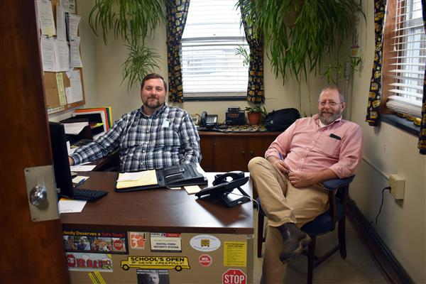 Eric Taylor and Jeff DeLucia sitting at the transportation supervisor desk in the bus garage