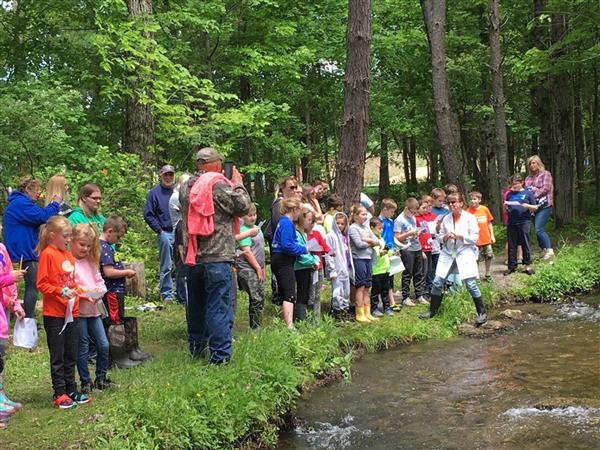 Students and others standing by stream before releasing trout