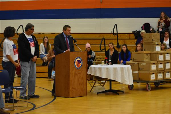 Poland Principal Greg Cuthbertson speaks at the Podium with Feed Our Vets represetnatives to his left and donated food nearby