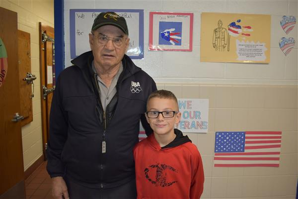 Local veteran poses with his grandson in the hallway before the Veterans Day Assembly
