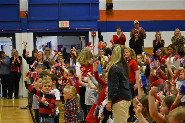 Students and staff wave red, white and blue ribbons