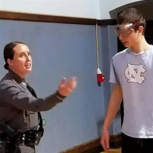 Student wears beer goggles with guidance from state trooper